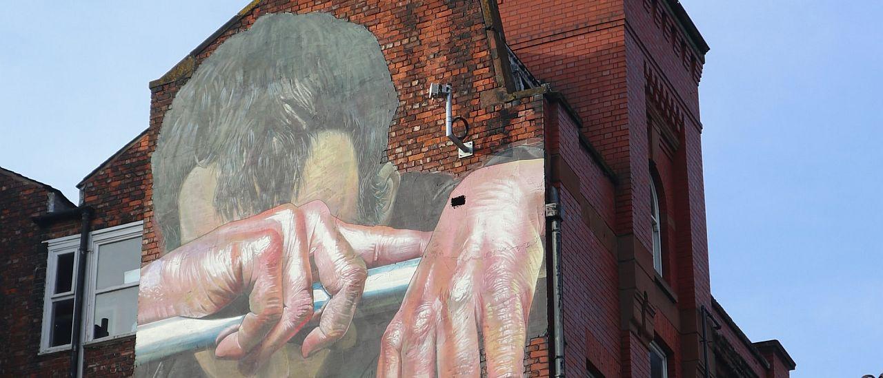 Sad man painting on building - Photo by Simon Watkinson on Unsplash