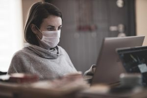 Woman with mask at laptop